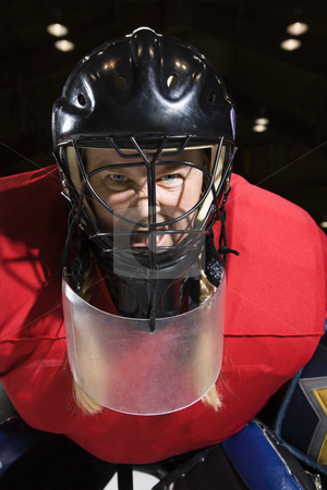 Woman hockey goalie. stock photo, Woman hockey goalie wearing helmet sneering looking intimidating. by Iofoto Images