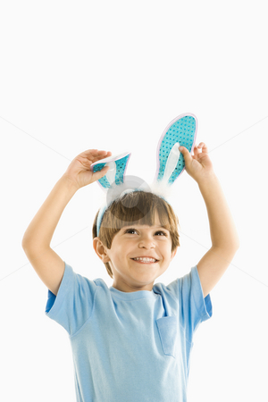 Boy in bunny ears. stock photo, Portrait of boy wearing rabbit ears smiling. by Iofoto Images