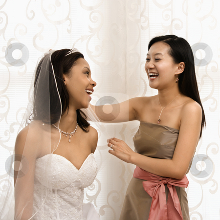 Laughing bride and bridesmaid. stock photo, Asian bridesmaid laughing with African-American bride. by Iofoto Images