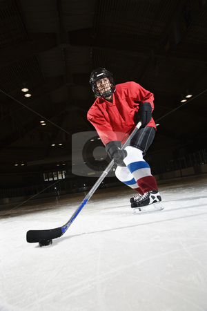 Woman hockey player. stock photo, Woman hockey player skating on ice lining up to shoot puck. by Iofoto Images