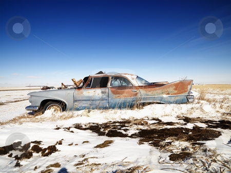 Rusted classic car. stock photo, Classic rusted car in snowy junkyard. by Iofoto Images