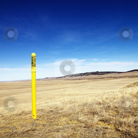 Petroleum warning pole. stock photo, Yellow petroleum warning pole in scenic landscape. by Iofoto Images