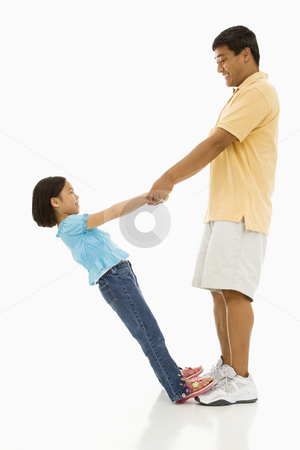 Daughter and father. stock photo, Asian daughter standing on father's feet holding his hands and leaning back. by Iofoto Images