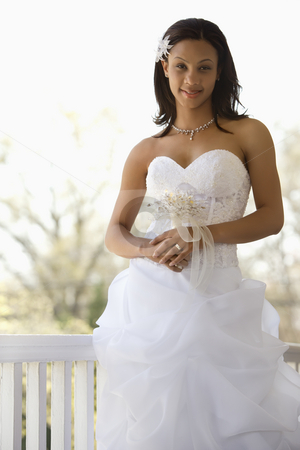 Bridal portrait. stock photo, Portrait of African-American bride leaning against railing. by Iofoto Images