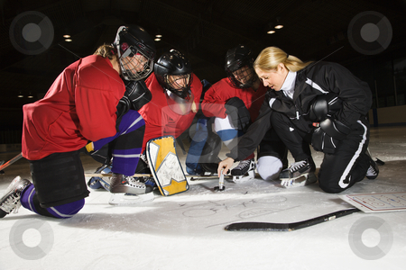 Women hockey players. stock photo, Women hockey players on ice looking at game plan with coach. by Iofoto Images