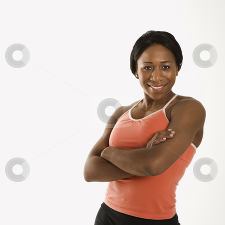 Woman with arms crossed. stock photo, African American young adult woman in athletic wear smiling at viewer with arms crossed. by Iofoto Images
