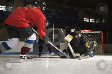 Women playing hockey. stock photo, Caucasian female hockey player trying to make goal as goalie protects the net. by Iofoto Images