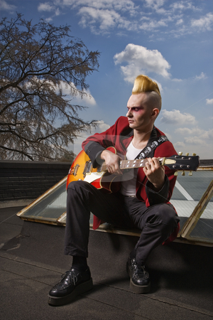 Punk playing guitar. stock photo, Portrait of a mid-adult Caucasian male punk  sitting on a skylight playing guitar. by Iofoto Images