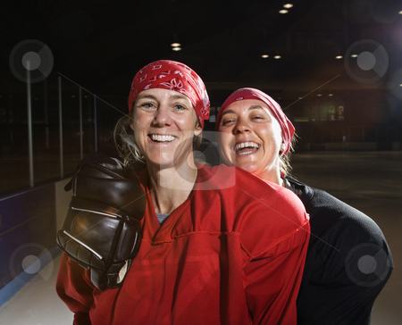 Female hockey players. stock photo, Women hockey players in uniform posing with helmets off on ice rink. by Iofoto Images