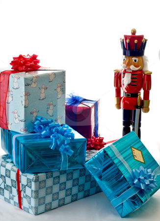 Nutcracker guarding presents stock photo, An  oversized nutcracker stands near a small pile of presents. by RCarner Photography