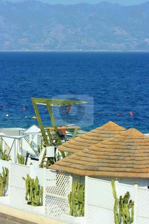 Fancy beach stock photo, Fancy beach with straw roofs and green lifeguard tower against Messina strait by Natalia Macheda
