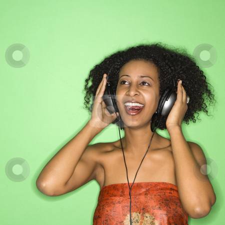 Woman listening to music. stock photo, African-American woman listening to music through headphones. by Iofoto Images
