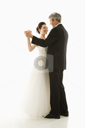 Bride and groom dancing. stock photo, Portrait of Caucasian groom and Asian bride dancing. by Iofoto Images