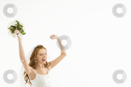 Cheering bride. stock photo, Portrait of Caucasian bride holding bouquet and raising arms. by Iofoto Images