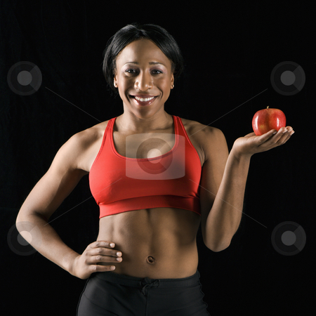 Athletic woman holding apple. stock photo, Smiling African American young adult woman holding apple with hand on hip. by Iofoto Images