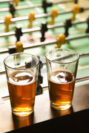 Two glasses of beer. stock photo, Two glasses of beer on foosball table. by Iofoto Images