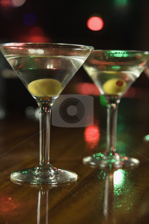 Two martinis on bar. stock photo, Two martinis with olives on bar with red and green lights in background. by Iofoto Images