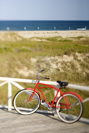 Red beach cruiser bicycle. stock photo, Bicycle leaning against rail on Bald Head Island, North Carolina by Iofoto Images