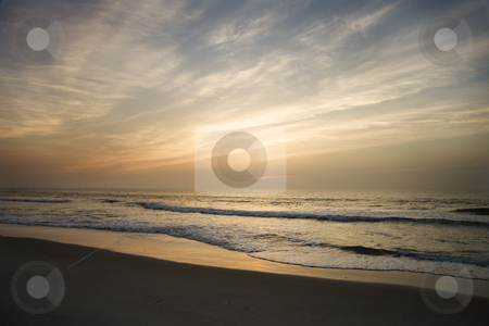 Beach at sunset. stock photo, Ocean waves lapping on the shore at sunset. by Iofoto Images
