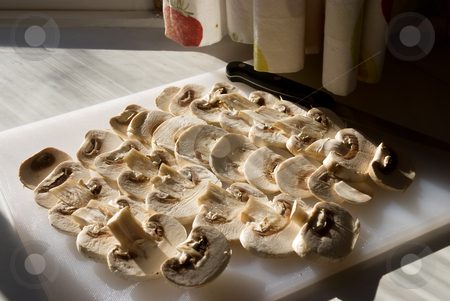 Country kitchen stock photo, Mushrooms sliced on a cutting board, lit with natural light from a kitchen window by Paul Phillips