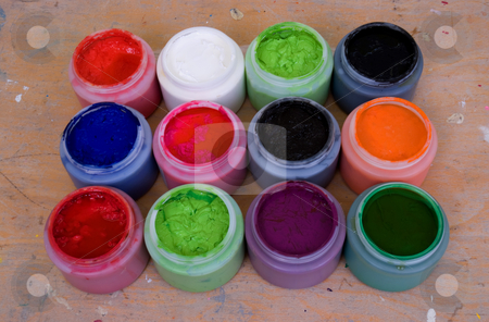 Acrylic Paint stock photo, Twelve tubs of acrylic paint on a work bench by Paul Phillips
