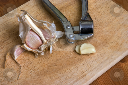 Press stock photo, Garlic cloves and a press on a chopping board by Paul Phillips
