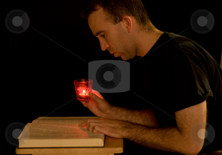 Reading By Candlelight stock photo, A young man trying to read a book in the dark by Richard Nelson