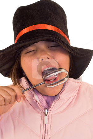 Winter Treat stock photo, A youn girl licking a beater, while wearing winter clothes by Richard Nelson