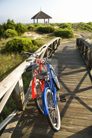 Bicycles at beach. stock photo, Image of red and blue bike leaning against railing of boardwalk. by Iofoto Images