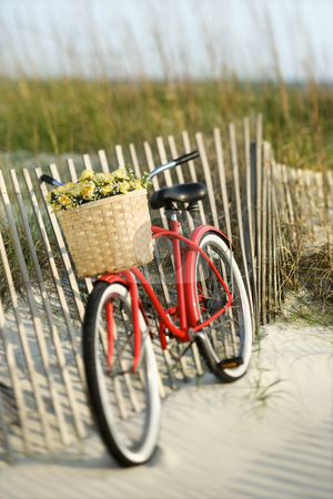 Bike on beach. stock photo, Red vintage bicycle with basket and flowers leaning against wooden fence at beach. by Iofoto Images
