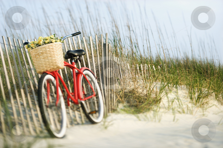 Bicycle with flowers. stock photo, Red vintage bicycle with basket and flowers lleaning against wooden fence at beach. by Iofoto Images