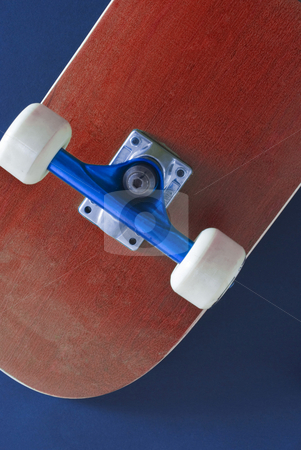 Skateboard stock photo, The underside of a red coloured skateboard on a blue background by Stephen Gibson
