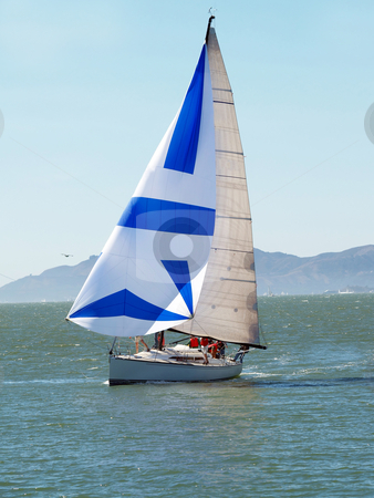 Sailboat on bay with spinnaker and crew on deck stock photo, Sailboat with sails up and crew on deck by Jeff Cleveland