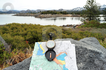Compass, Map And Lake stock photo, A hiking map and compass overlooking a lake in the Califirnia sierra nevada mountains. by Lynn Bendickson