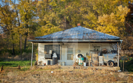 Posted House stock photo, The sun sets on an old abandoned house with fall leaves in the background by Mitch Aunger