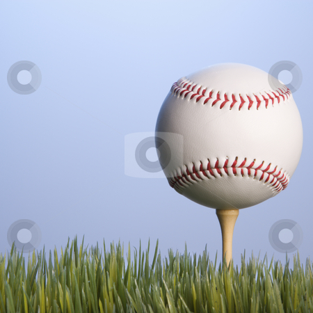 Baseball on tee. stock photo, Studio shot of baseball resting on golf tee in grass. by Iofoto Images