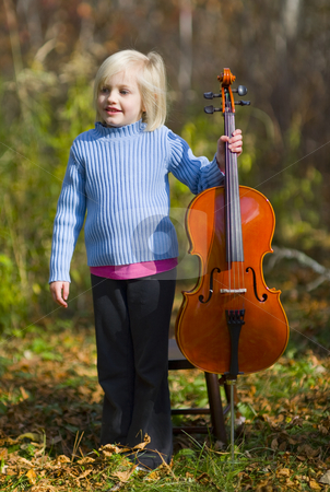 Child Standing With Cello stock photo, A child standing with her cello outside on a crisp autumn day. by John McLaird