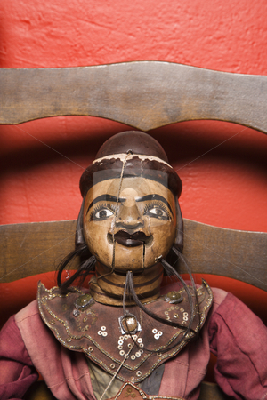 Wooden puppet. stock photo, Close up of wooden puppet sitting on chair. by Iofoto Images