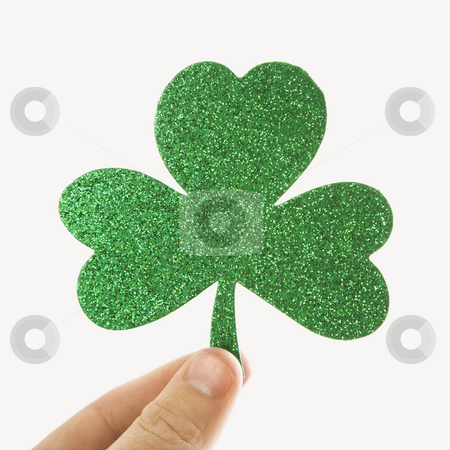 Green glitter shamrock. stock photo, Hand holding a green glitter paper shamrock. by Iofoto Images