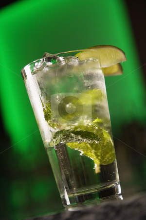 Mixed drink cocktail. stock photo, Still life of mixed drink cocktail with mint leaves and fruit garnish against glowing green background. by Iofoto Images