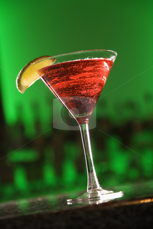 Martini cocktail. stock photo, Still life of martini cocktail with fruit garnish against glowing green background. by Iofoto Images