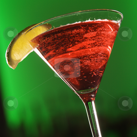 Martini mixed drink. stock photo, Still life of martini cocktail with  fruit garnish against glowing green background. by Iofoto Images