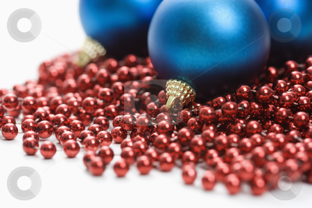 Christmas ornaments. stock photo, Still life of large blue Christmas ornaments and strings of red beads. by Iofoto Images