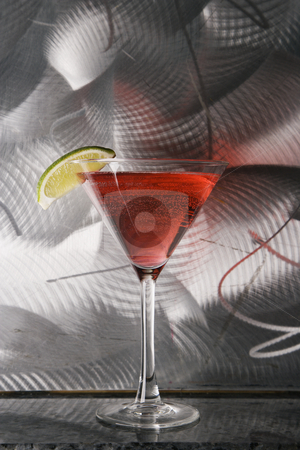 Still life of martini. stock photo, Still life of martini mixed drink with raspberry fruit agaisnt textured metallic background. by Iofoto Images