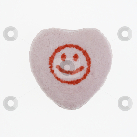 Candy heart on white. stock photo, Purple candy heart with smiley face against white background. by Iofoto Images