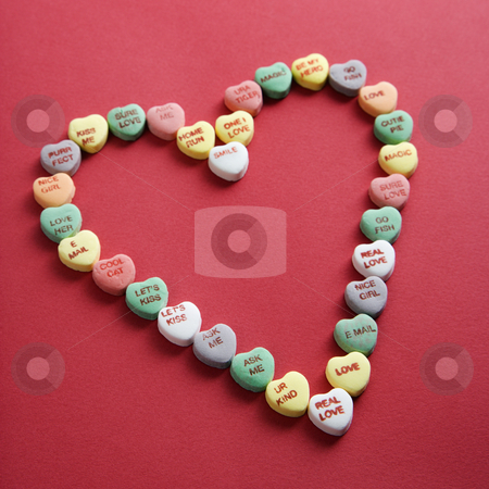 Candy hearts on red. stock photo, Colorful candy hearts with sayings on them arranged in shape of heart on red background. by Iofoto Images