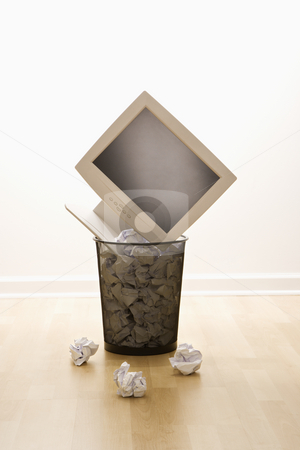 Computer in trash can. stock photo, Computer monitor in trash can surrounded by crumpled up paper. by Iofoto Images