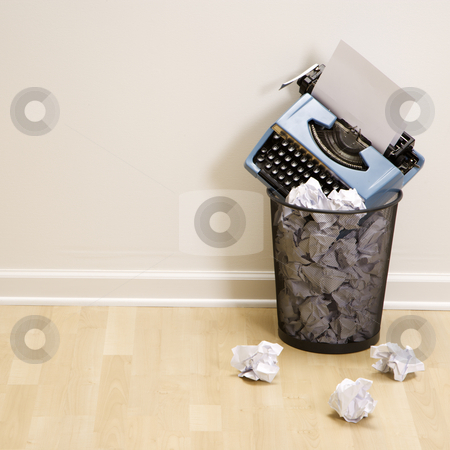 Typewriter in trash can. stock photo, Old fashioned typewriter in trash can surrounded by crumpled up paper. by Iofoto Images