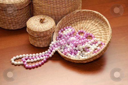 White and pink pearls stock photo, White and pink pearls on basket cover over wooden background by Julija Sapic