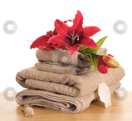Peace and Tranquility stock photo, Some artificial lilies resting on some towels along with some seashells by Richard Nelson